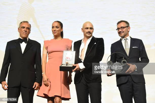 James Franco poses with his award for JaegerLeCoultre Glory to the Filmmaker 2014 with director of the Venice Film Festival Alberto Barbera Carmen...