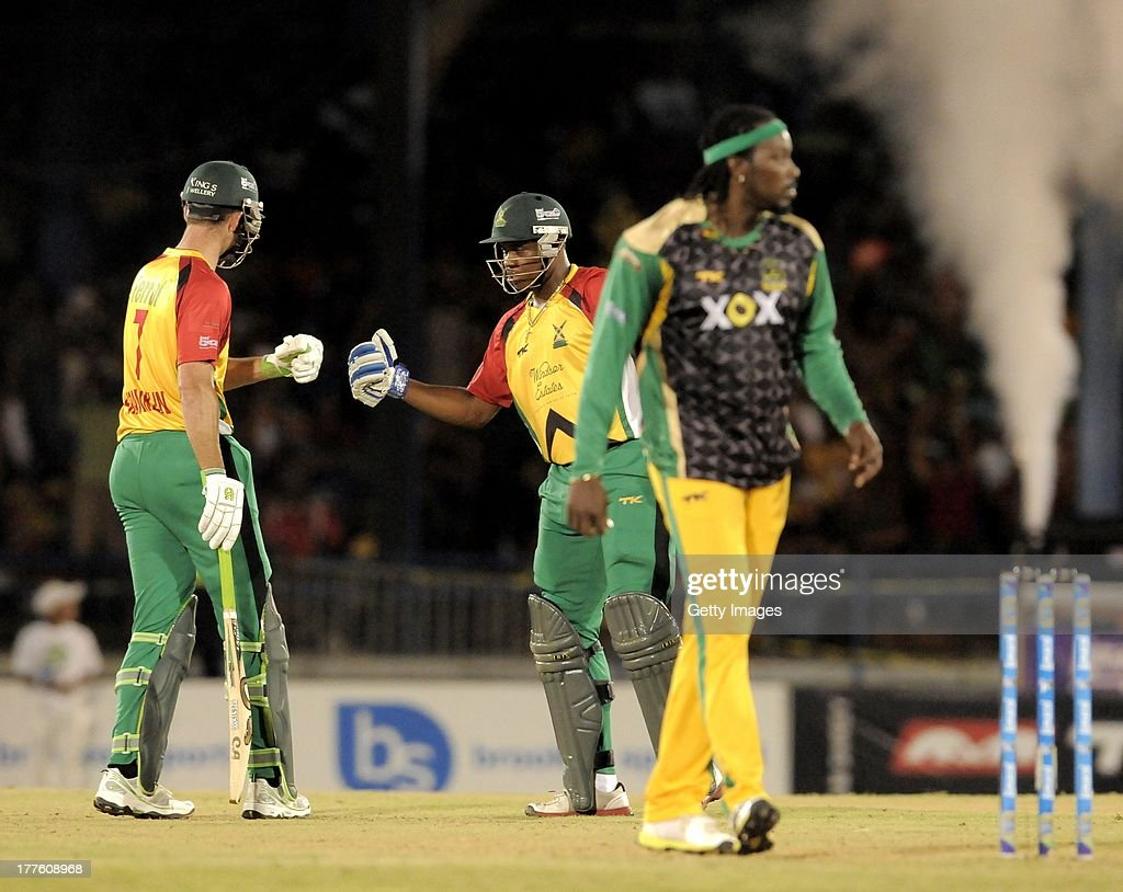 James Franklyn (L) and Christopher Barnwell (C) of Guyana Amazon Warriors knock gloves for 4 runs off Jamaica Tallawahs Chris Gayle (R) during the Final of the Caribbean Premier League between Guyana Amazon Warriors v Jamaica Tallawahs at Queens Park Oval on August 24, 2013 in Port of Spain, Trinidad and Tobago.
