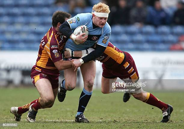 James Graham of St Helens is tackled by John Skandalis and Stuart Jones of Huddersfield during the Engage Super League match between Huddersfield...