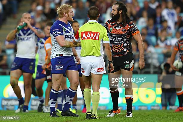 James Graham of the Bulldogs and Aaron Woods of the Tigers exchange words as the referee watches on during the round 10 NRL match between the Wests...
