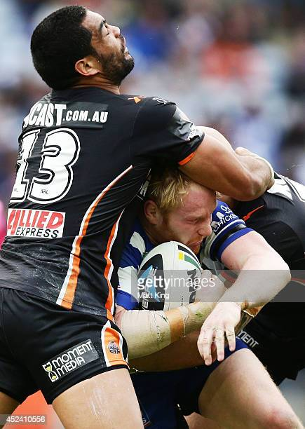 James Graham of the Bulldogs is tackled by Adam Blair of the Tigers during the round 19 NRL match between the Wests Tigers and the Canterbury...