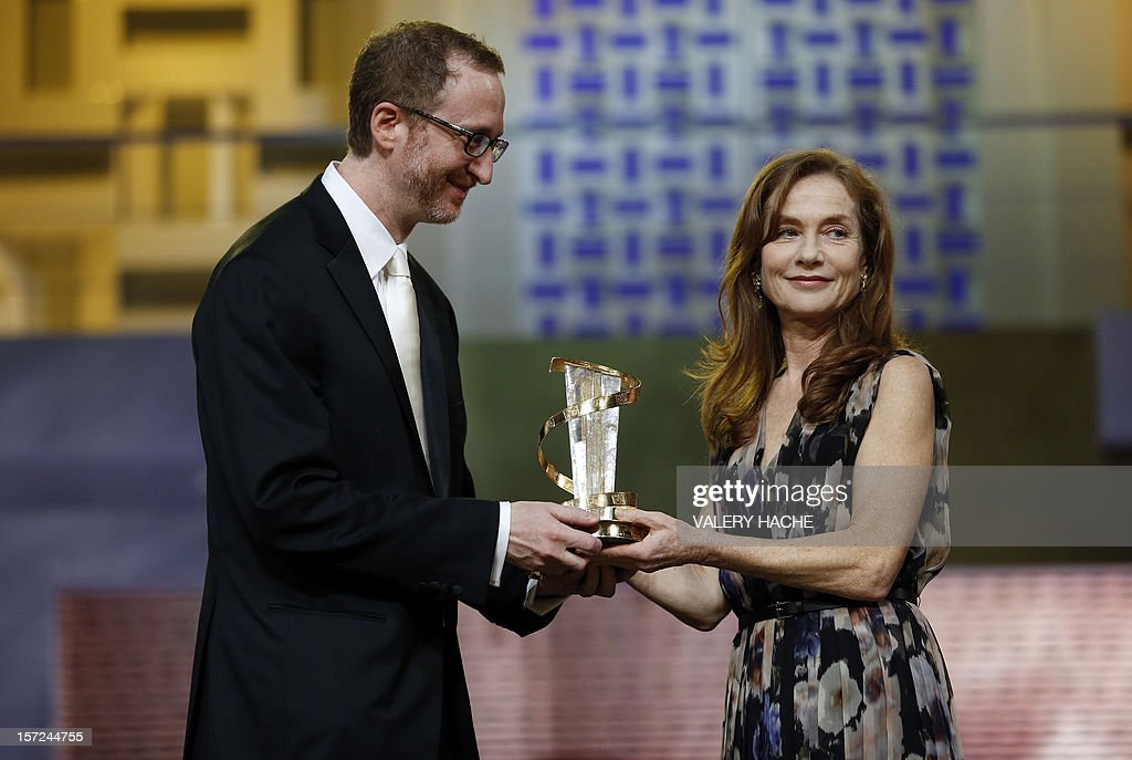 James Gray delivers a trophy to French actress Isabelle Huppert during the opening ceremony of the 12th Marrakesh International Film Festival on November 30, 2012 in Marrakesh. AFP PHOTO / VALERY HACHE