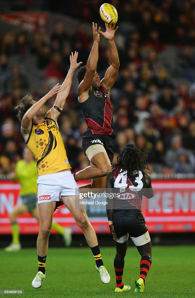 James Gwilt of the Bombers marks the ball against Tyrone Vickery of the Tigers during the round 10 AFL match between the Essendon Bombers and the Richmond Tigers at Melbourne Cricket Ground on May 28, 2016 in Melbourne, Australia.