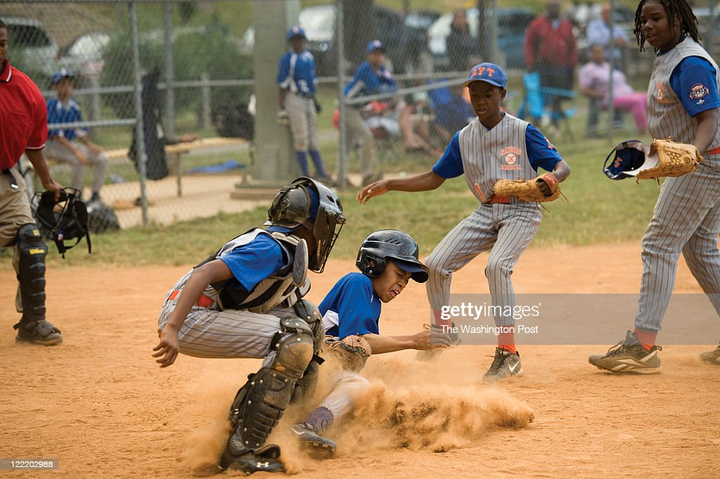 James Hampton, left, tries to tag out #12 for the Takoma Rangers as Derquan Washington, center, and Clint Broadus, right, look on during a playoff game at the Taft Recreation Center on Tuesday June 14, 2011 in Washington, DC. The AYT #14 Raiders won 16-1. #12 was safe and represented the Rangers only run of the game. This game was in the Cal Ripken Division of the Babe Ruth League.