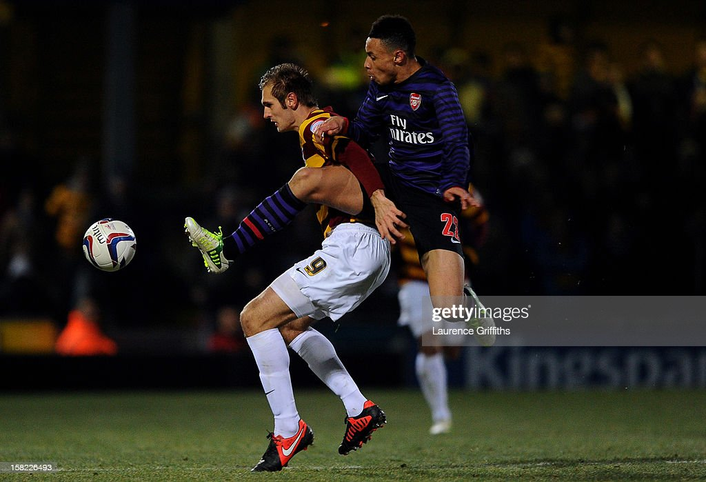 James Hanson of Bradford is tackled by Francis Coquelin of Arsenal during the Capital One Cup quarter final match between Bradford City and Arsenal at the Coral Windows Stadium, Valley Parade on December 11, 2012 in Bradford, England.
