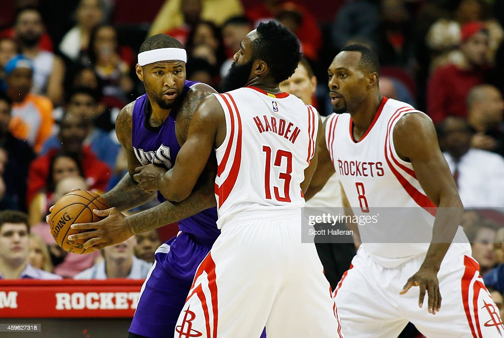 James Harden and Joey Dorsey of the Houston Rockets defend against DeMarcus Cousins of the Sacramento Kings during their game at the Toyota Center on...
