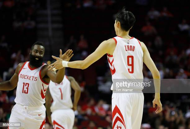 James Harden of Houston Rockets congratulates Zhou Qi after scoring in the second quarter against the Shanghai Sharks at Toyota Center on October 5...