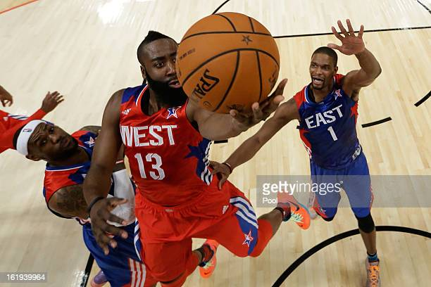 James Harden of the Houston Rockets and the Western Conference goes up for a shot between LeBron James and Chris Bosh of the Eastern Conference...