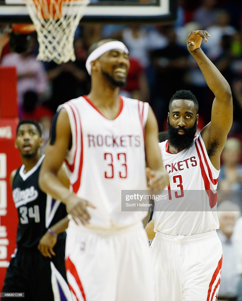 James Harden #13 of the Houston Rockets celebrates a play with teammate Corey Brewer #33 as Jason Thompson #34 of the Sacramento Kings looks on during their game at the Toyota Center on April 1, 2015 in Houston, Texas.