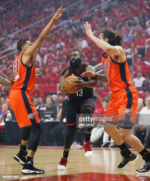 James Harden of the Houston Rockets dribbles between Andre Roberson of the Oklahoma City Thunder and Steven Adams during Game One of the first round...