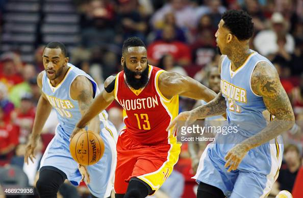 James Harden of the Houston Rockets dribbles between Darrell Arthur and Wilson Chandler of the Denver Nuggets during their game at the Toyota Center...