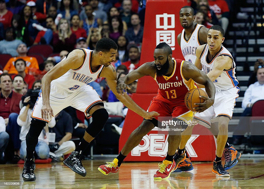 James Harden #13 of the Houston Rockets drives against Thabo Sefolosha #2 of the Oklahoma City Thunder at Toyota Center on February 20, 2013 in Houston, Texas.