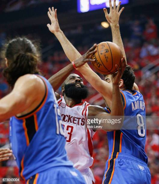 James Harden of the Houston Rockets drives between Alex Abrines of the Oklahoma City Thunder and Steven Adams during Game Five of the Western...