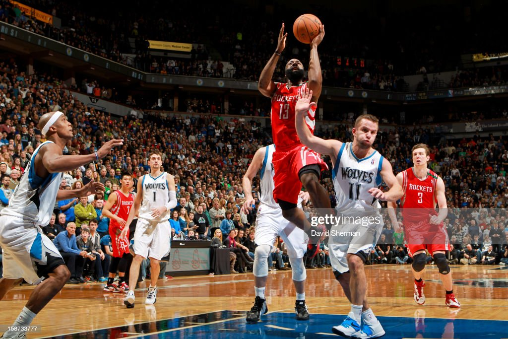 James Harden #13 of the Houston Rockets drives to the basket against Jose Juan Barea #11 of the Minnesota Timberwolves on December 26, 2012 at Target Center in Minneapolis, Minnesota.