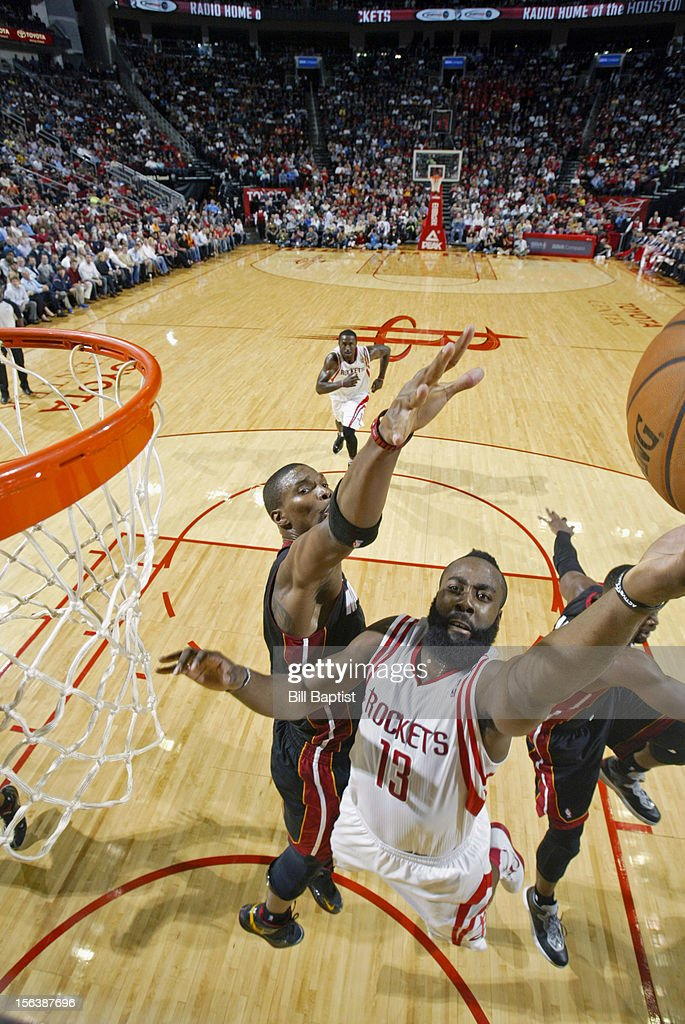 James Harden #13 of the Houston Rockets drives to the basket against Chris Bosh #1 of the Miami Heat on November 12, 2012 at the Toyota Center in Houston, Texas.