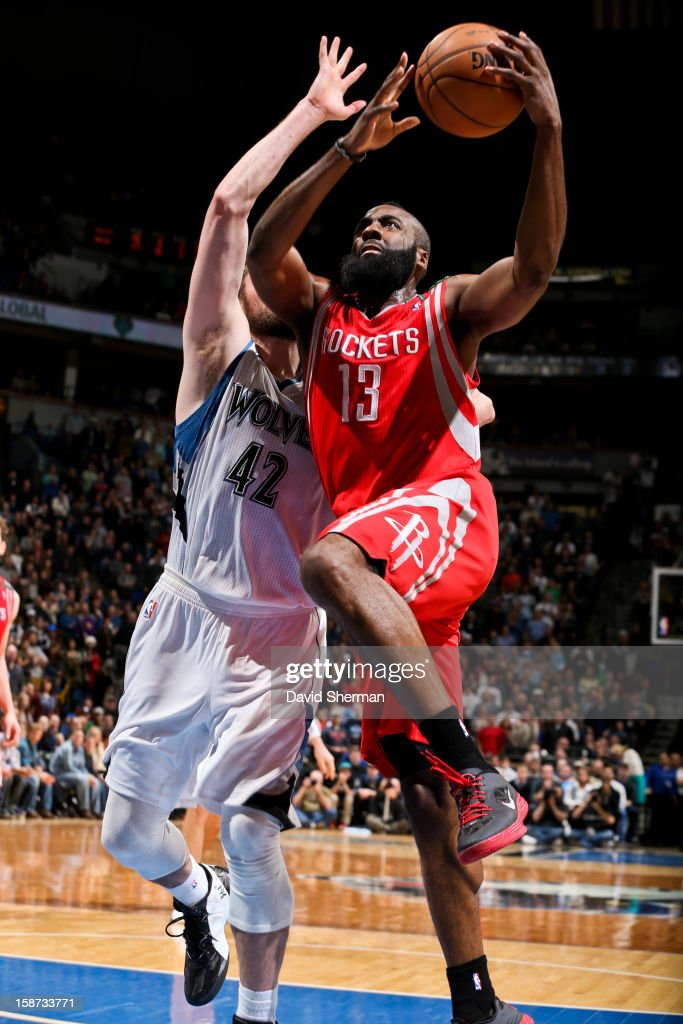 James Harden #13 of the Houston Rockets drives to the basket against Kevin Love #42 of the Minnesota Timberwolves on December 26, 2012 at Target Center in Minneapolis, Minnesota.