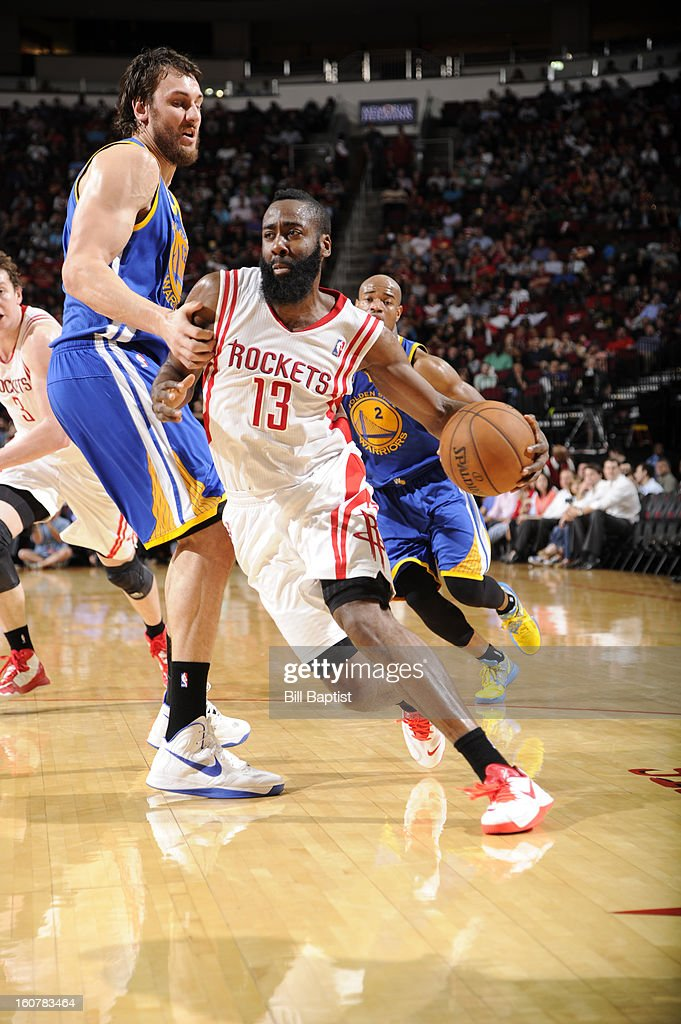 James Harden #13 of the Houston Rockets drives to the basket against Andrew Bogut #12 of the Golden State Warriors on February 5, 2013 at the Toyota Center in Houston, Texas.