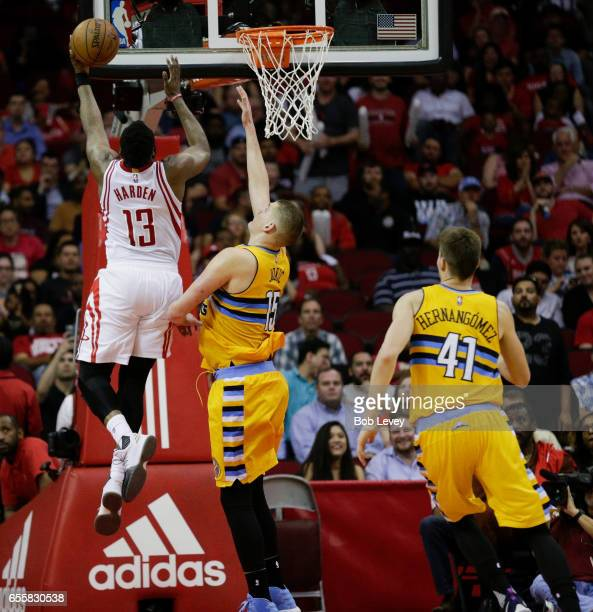 James Harden of the Houston Rockets drives to the basket past Nikola Jokic of the Denver Nuggets for a layup during the fourth quarter as Juancho...