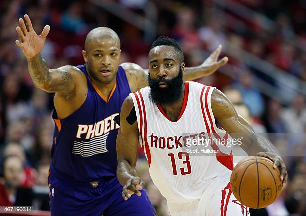 James Harden of the Houston Rockets drives with the basketball in front of PJ Tucker of the Phoenix Suns during their game at the Toyota Center on...
