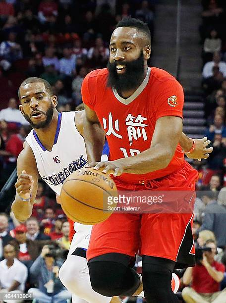 James Harden of the Houston Rockets drives with the basketball past Chris Paul of the Los Angeles Clippers during their game at the Toyota Center on...