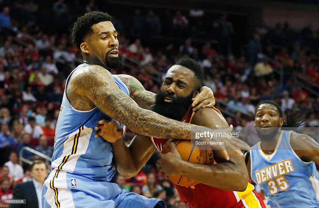James Harden of the Houston Rockets gets fouled by Wilson Chandler of the Denver Nuggets during their game at the Toyota Center on March 19 2015 in...