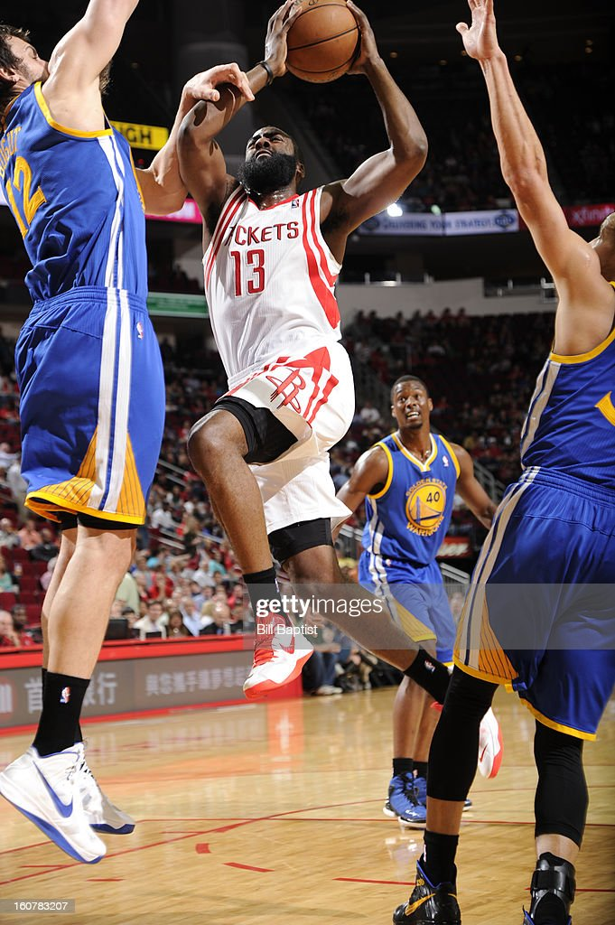 James Harden #13 of the Houston Rockets goes to the basket against Andrew Bogut #12 of the Golden State Warriors on February 5, 2013 at the Toyota Center in Houston, Texas.