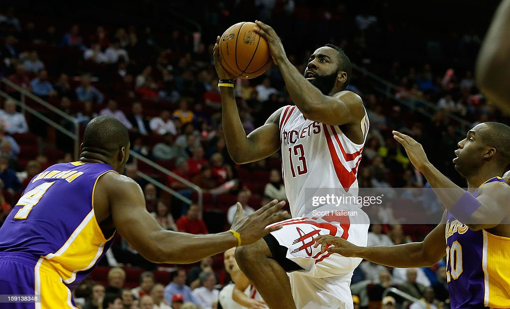 James Harden #13 of the Houston Rockets goes up for a shot against Antawn Jamison #4 and Jodie Meeks #20 of the Los Angeles Lakers at Toyota Center on January 8, 2013 in Houston, Texas.