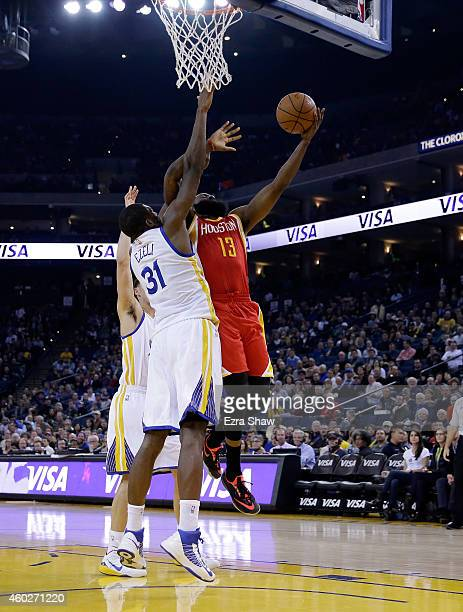 James Harden of the Houston Rockets goes up for a shot against Festus Ezeli of the Golden State Warriors at ORACLE Arena on December 10 2014 in...