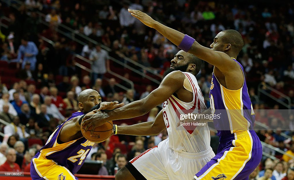 James Harden #13 of the Houston Rockets goes up for a shot against Kobe Bryant #24 and Jodie Meeks #20 of the Los Angeles Lakers at Toyota Center on January 8, 2013 in Houston, Texas.