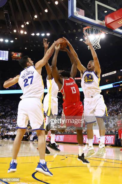 James Harden of the Houston Rockets goes up for a shot against Zaza Pachulia and Klay Thompson of the Golden State Warriors during their NBA game at...