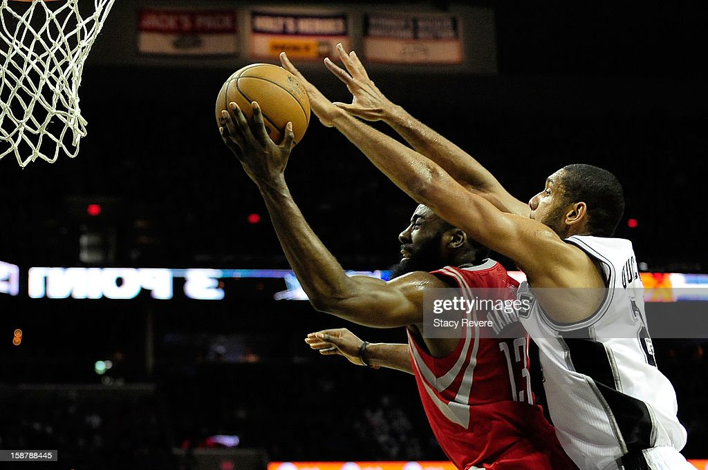James Harden #13 of the Houston Rockets is defended by Tim Duncan #21 of the San Antonio Spurs during a game at AT&T Center on December 28, 2012 in San Antonio, Texas. San Antonio won the game 122-116.