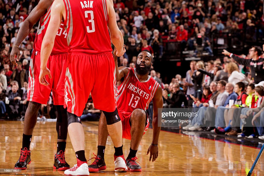 <a gi-track='captionPersonalityLinkClicked' href=/galleries/search?phrase=James+Harden&family=editorial&specificpeople=4215938 ng-click='$event.stopPropagation()'>James Harden</a> #13 of the Houston Rockets is helped up by teammates <a gi-track='captionPersonalityLinkClicked' href=/galleries/search?phrase=Omer+Asik&family=editorial&specificpeople=4946055 ng-click='$event.stopPropagation()'>Omer Asik</a> #3 and <a gi-track='captionPersonalityLinkClicked' href=/galleries/search?phrase=Patrick+Patterson&family=editorial&specificpeople=2928099 ng-click='$event.stopPropagation()'>Patrick Patterson</a> #54 after falling against the Portland Trail Blazers on November 16, 2012 at the Rose Garden Arena in Portland, Oregon.