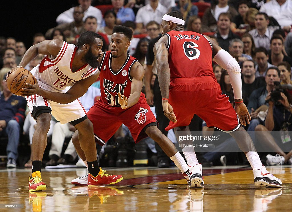 James Harden of the Houston Rockets looks to pass against Norris Coles, center, and LeBron James, right, during the second quarter at the AmericanAirlines Arena in Miami, Florida, Wednesday, February 6, 2013. The Miami Heat defeated the Houston Rockets 114-108.