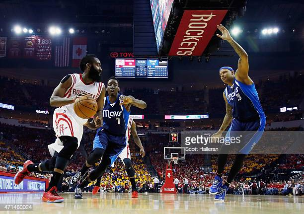 James Harden of the Houston Rockets looks to pass the basketball in front of AlFarouq Aminu and Charlie Villanueva of the Dallas Mavericks of the...