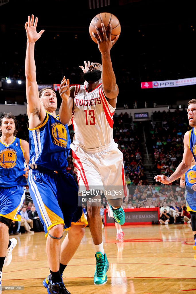 James Harden #13 of the Houston Rockets shoots a layup against Klay Thompson #11 of the Golden State Warriors on March 17, 2013 at the Toyota Center in Houston, Texas.