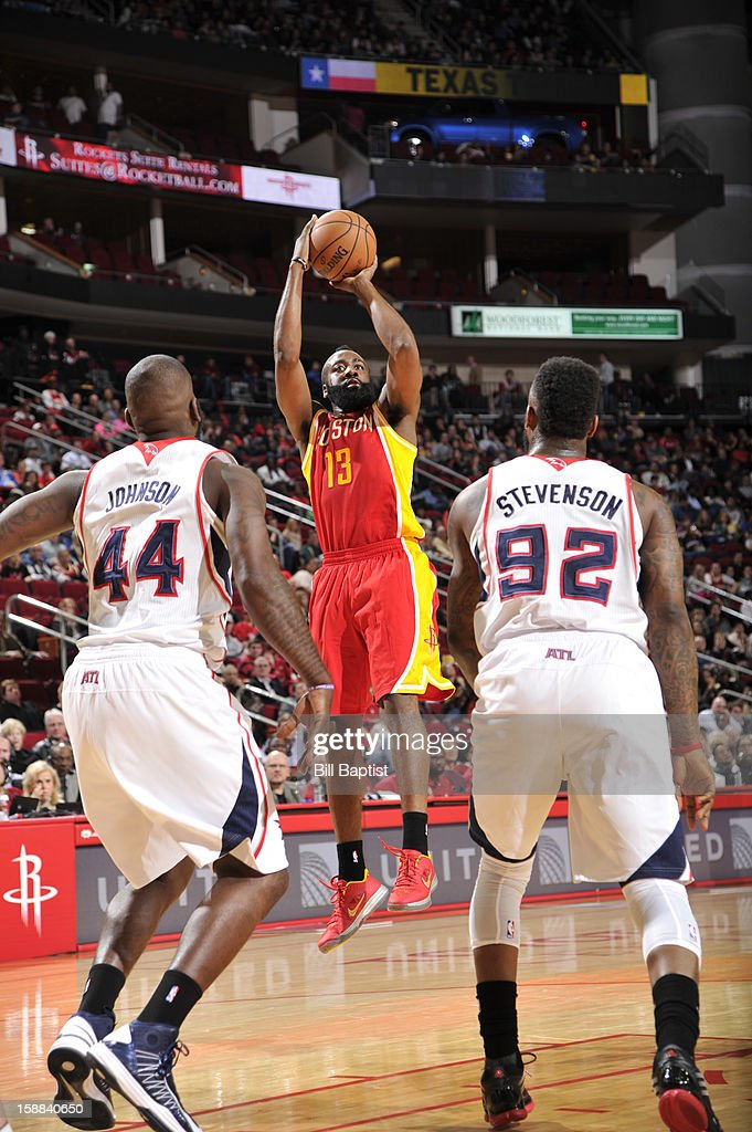 James Harden #13 of the Houston Rockets shoots the ball over Ivan Johnson #44 and DeShawn Stevenson #92 of the Atlanta Hawks on December 31, 2012 at the Toyota Center in Houston, Texas.