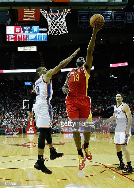 James Harden of the Houston Rockets takes a shot against Russell Westbrook of the Oklahoma City Thunder at Toyota Center on February 20 2013 in...