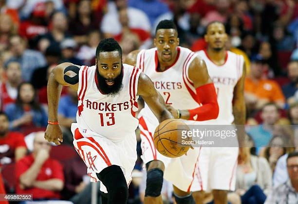 James Harden of the Houston Rockets takes the baskeball upcourt as Dwight Howard and Trevor Ariza look on during their game against the Utah Jazzat...