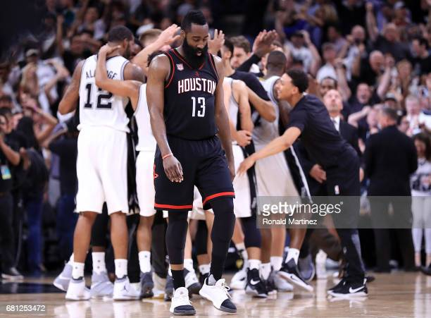 James Harden of the Houston Rockets walks off the court as the San Antonio Spurs celebrate a win in overtime during Game Five of the Western...