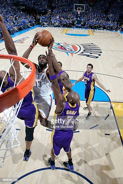 James Harden of the Oklahoma City Thunder goes to the basket against Andrew Bynum and Lamar Odom of the Los Angeles Lakers in Game Six of the Western...