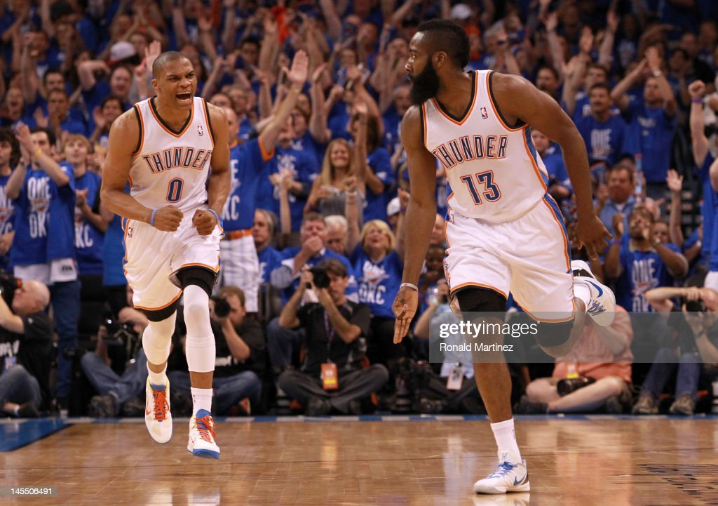 James Harden #13 reacts after making a three-pointer alongside teammate Russell Westbrook #0 of the Oklahoma City Thunder in the first half against the San Antonio Spurs in Game Three of the Western Conference Finals of the 2012 NBA Playoffs at Chesapeake Energy Arena on May 31, 2012 in Oklahoma City, Oklahoma.