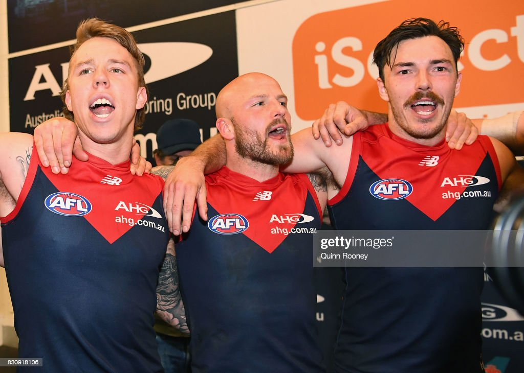 James Harmes, Nathan Jones and Michael Hibberd of the Demons sing the song in the rooms after winning the round 21 AFL match between the Melbourne Demons and the St Kilda Saints at Melbourne Cricket Ground on August 13, 2017 in Melbourne, Australia.