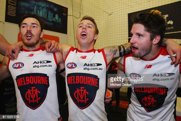 James Harmes of the Demons hugs Michael Hibberd and Jesse Hogan as they sing the club song after winning during the round 16 AFL match between the...