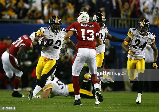 James Harrison of the Pittsburgh Steelers runs back an interception for 100 yards to score a touchdown in the second quarter against Kurt Warner of...