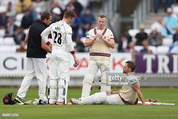 James Hildreth of Somerset struggling with an injured right foot takes the weight off his feet alongside Chris Rogers and runner Tom Abell during a...
