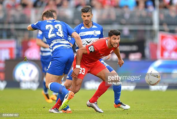 James Holland of Duisburg Elia Soriano of Wuerzburg and Enis Hajri of Duisburg tussle for the ball during the Second Bundesliga Play Off first leg...