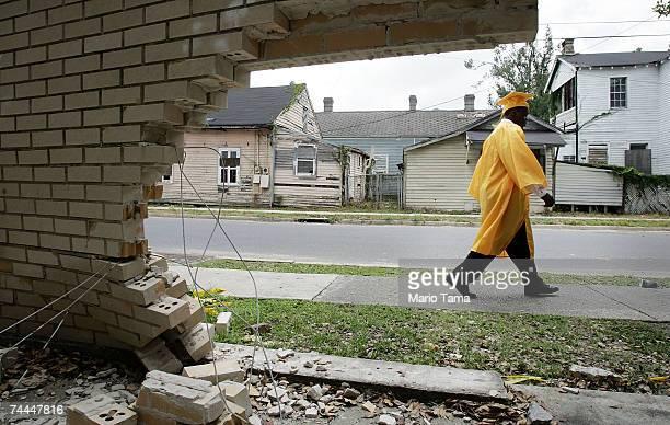 James Holloway from John McDonogh Senior High School's first graduating class since Hurricane Katrina walks past a damaged wall on his way his...