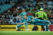 James Hopes of the Heat dives to run out Usman Khawaja of the Thunder during the Big Bash League match between the Sydney Thunder and the Brisbane...