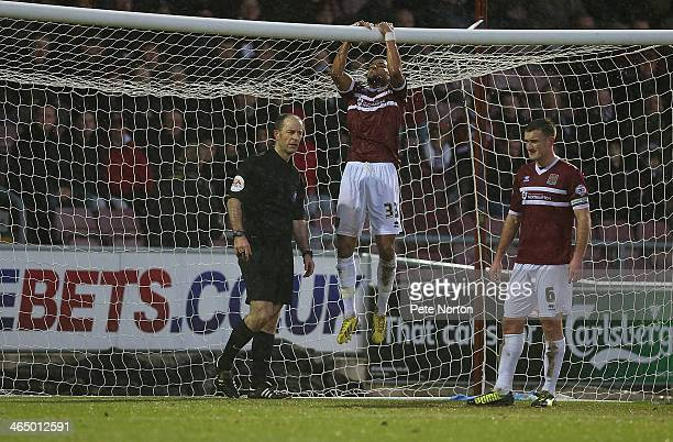 James Hurst of Northampton Town attempts to reattach the net to the crossbar as team mate Lee Collins and referee Graham Horwood look on during the...