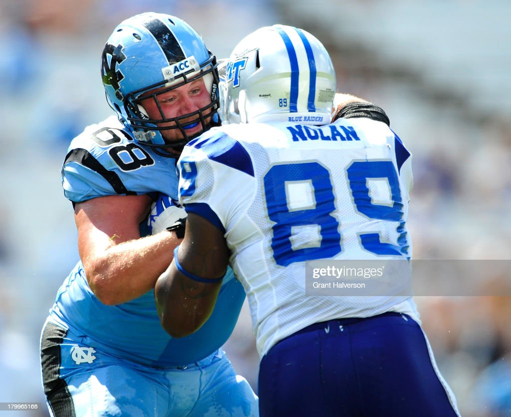 James Hurst #68 of the North Carolina Tar Heels pass-blocks Dearco Nolan #89 of the Middle Tennessee State Blue Raiders during play at Kenan Stadium on September 7, 2013 in Chapel Hill, North Carolina. North Carolina won 40-20.